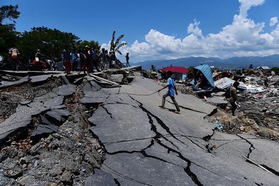 Ljudi prelaze oštećenu cestu u Balaroi nakon potresa i cunamija koji su pogodili Sulawesi 28. rujna 2018.