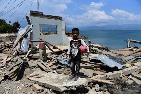 Desetogodišnji dječak Rido Saputra 3. listopada 2018. stoji ispred ruševina svoje kuće u pokrajini Donggala, koju je uništio cunami.