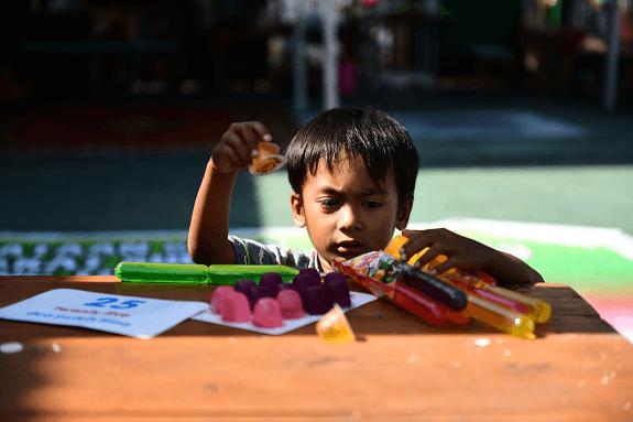 Četverogodišnji dječak Muhamad Faiq 2. listopada 2018. uzima slatkiš od želatine jer humanitarne pošiljke hrane još nisu stigle u četvrt Istočni Lolu grada Palua.