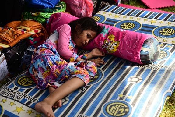Hilda (6) plače dok čeka majku koja traži brata nestalog u potresu. 02.10., izbjeglički kamp, Palu, središnji Sulawesi.